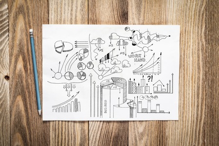 Financial charts and graphs pencil hand drawn with group of business doodles. Workplace with paper and pencil lying on wooden desk. Investment risk analysis. Business presentation concept
