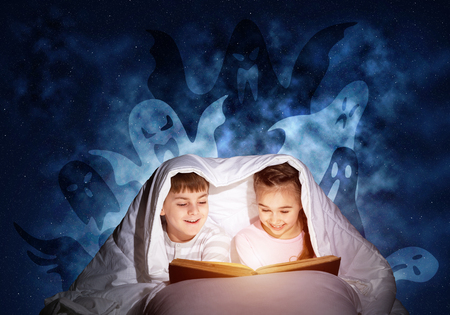 Happy little kids reading magic fairy tales in bed. Brother and sister together hiding under blanket. Little friends in pajamas with open big book and imaginary monsters on deep blue background.