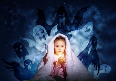 Scared girl with flashlight hiding under blanket from imaginary ghosts. Kid sitting in bed on night sky background. Covered child in pajamas not sleep at night. Mysterious phantoms in darkness. Zdjęcie Seryjne