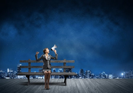 Business woman with megaphone sitting on wooden bench. Female speaker shouting in loudspeaker outdoors. Modern cityscape panorama at night. Business marketing and announcement.