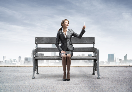 Business woman taking selfie photo or chatting with smartphone. Attractive girl using mobile phone on wooden bench. Mobile marketing and communication. Modern cityline panorama with cloudy sky.