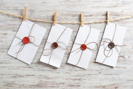 White classic envelopes hanging on twine rope with clothespins. Vintage declaration of love on wooden painted background. Retro letter envelope with sealing wax stamp. Romantic wedding invitation. Stock Photo
