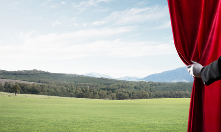 Human hand in glove opens red velvet curtain to landscape Stock Photo - 123986122