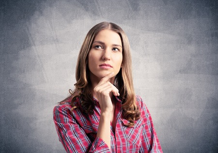 Brown haired woman looks pensive upwards and tries to remember something. Puzzled girl has serious facial expression. Portrait of beautiful woman wears red checkered shirt on grey background.