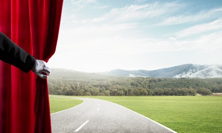 Human hand in glove opens red velvet curtain to landscape Stock Photo - 123986155