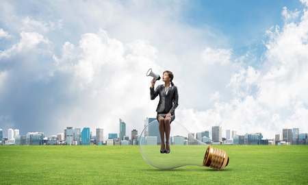 Young woman with megaphone sitting on big light bulb. Female speaker on background of modern downtown, green grass and blue sky. Girl shouting in loudspeaker. Business marketing and announcement.