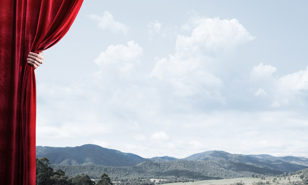 Human hand opens red curtain on natural landscape background Stock Photo