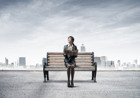 Young woman holding open book and sitting on wooden bench outdoors. Beautiful girl in business suit looking up on background modern cityline panorama with cloudy sky. Business education and growth.