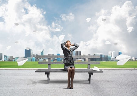 Stressful woman sitting on wooden bench. Emotional screaming girl keeps hands on head. Businesswoman in despair on background modern cityline panorama with flying paper planes. Woman call for help. Stockfoto - 124016679