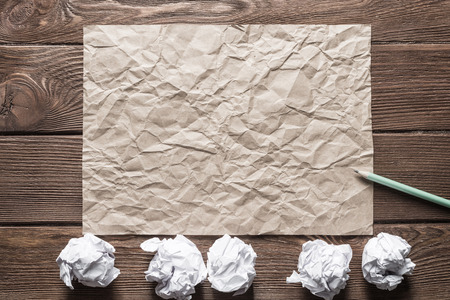 Crumpled brown paper sheet and pencil on wooden table Stock Photo - 124209623