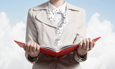 Attractive woman holding open notebook with question mark from cubes.