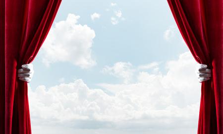 Human hand in glove opens red velvet curtain on blue sky Foto de archivo - 124209629