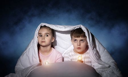 Children with flashlights lying in bed. Little sister and brother hiding under blanket together.
