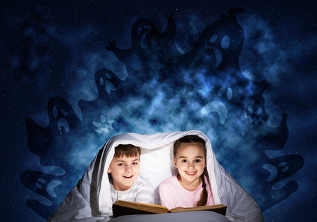 Happy little kids reading magic fairy tales in bed.