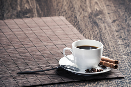 Cup of espresso coffee on wooden table with bamboo mat.