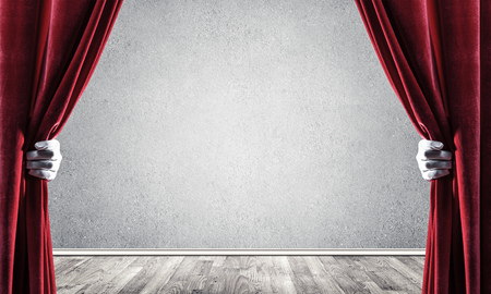 Close up of hands in white glove open red velvet curtain