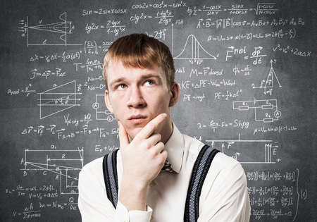 Redhead student looks pensively upwards and tries to remember something.