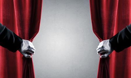 Cerca de la mano en guante blanco abrir cortina de terciopelo rojo