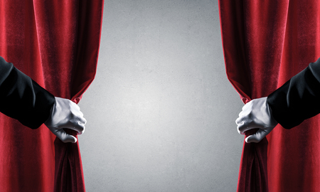 Close up of hand in white glove open red velvet curtain