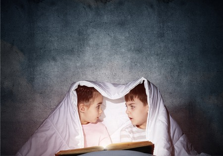 Surprised children reading scary stories in bed before going to sleep. Amazed girl and boy in pajamas hiding under blanket together. Covered kids with open book not sleep at night. Happy childhood