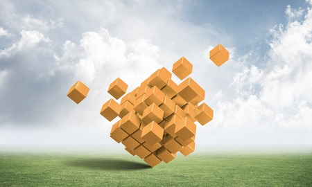 Abstract orange cubes on green meadow. Digital technology and innovation solutions.