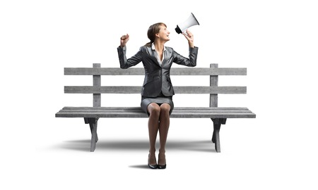 Young woman shouting into megaphone on wooden bench. Beautiful girl in business suit sitting on bench. Pretty businesswoman screaming with loudspeaker isolated on white. Promotion and announcement 版權商用圖片