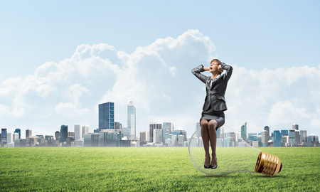Stressful woman sitting on big light bulb. Screaming girl keeps hands on head. Businesswoman in despair on background of modern downtown, green grass and blue sky. Panic attack and feeling of pain