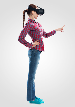 Young woman wearing VR goggles and gaming in interactive game. Lady in checkered shirt and jeans gesturing in air. Studio photo by girl against gray background. Digital entertainment in cyberspace
