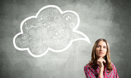 Serious woman looks pensive upwards and thinking something. Speech bubble full of business diagrams doodles on grey wall. Puzzled girl has serious facial expression. Woman wears red checkered shirt Stock Photo