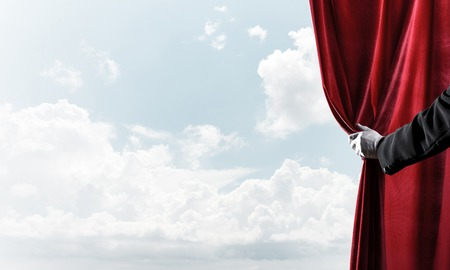 Human hand in glove opens red velvet curtain on blue sky background Stock Photo