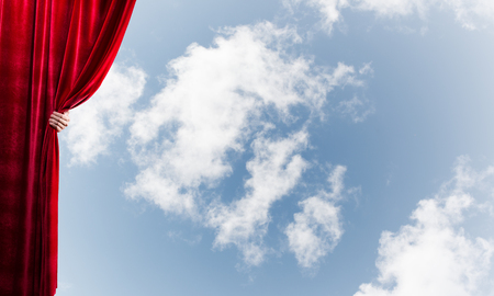 Human hand opens red velvet curtain on blue sky background Stock Photo - 124383964