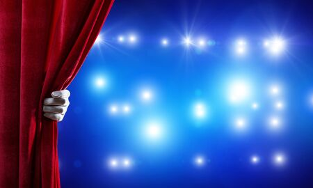 Close up of hand in white glove open red velvet curtain to stage Stock Photo