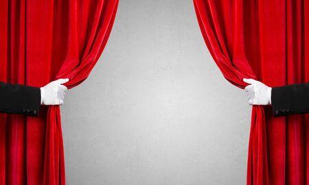 Cerca de dos manos en guante blanco abrir cortina de terciopelo rojo