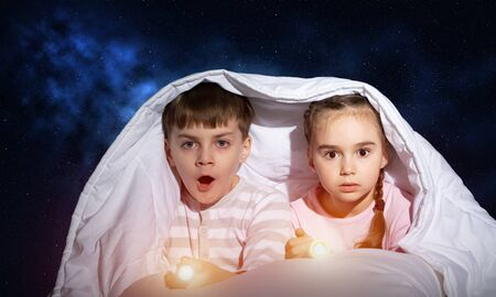 Scared children with flashlights lying in bed. Little sister and brother hiding under blanket together. Covered kids afraid of dark at night on background of deep blue sky. Night terrors of child.