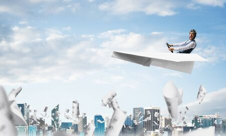 Screaming pilot sitting in paper plane and holding steering wheel. Aviator driving paper plane in blue sky above falling paper sheets with infographics. Cityscape with skyscrapers and office buildings Banco de Imagens
