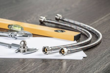 Steel water fittings for hydraulic system. Plumbing pipeline parts, calipers and level tool laying on table. Building company engineering and construction. Professional plumbing technical servicing. Stock Photo - 124549164