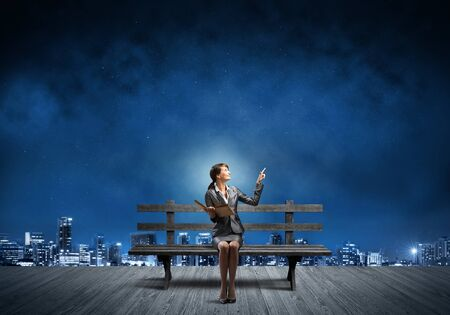 Young woman holding open book on wooden bench outdoor. Beautiful girl in business suit finger pointing in night sky. Modern cityscape panorama at night. Business education and knowledge.