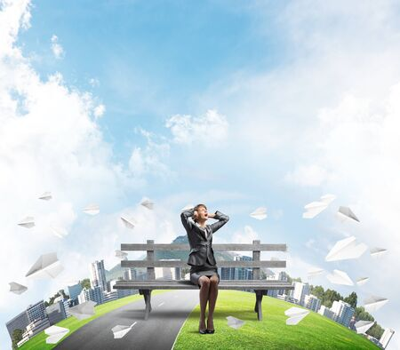 Stressful woman sitting on wooden bench. Emotional screaming girl keeps hands on head. Businesswoman in despair. City panorama with round horizon of world and flying paper planes. Woman call for help. Stockfoto - 124549142