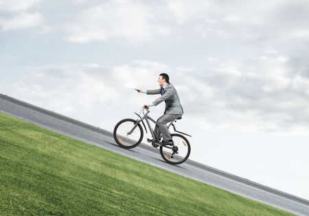 Businessman with paper documents in hand going uphill on bike. Paperwork express service. Corporate employee in grey business suit on bicycle riding up on mountain road. Accounting deadline concept.