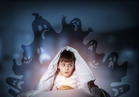 Niño sorprendido con linterna escondida debajo de una manta. Niño asombrado sentado en su cama en casa. Miedo a la oscuridad. Niño en pijama con miedo a los fantasmas por la noche. Fantasía e imaginación de pesadilla.
