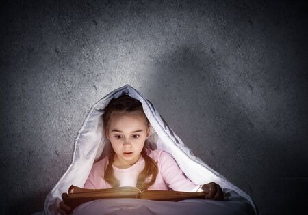Engrossed little girl reading book in bed before going to sleep. Pretty kid with flashlight hiding under blanket. Beautiful girl in pajamas on background of grey wall. Child reading fairy tales. Stock Photo