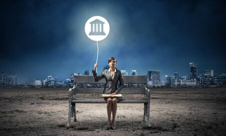 Young woman with open book on wooden bench outdoor. Legal assistance and representation. Beautiful girl with court of justice or bank symbol in night sky. Modern cityscape panorama at night.