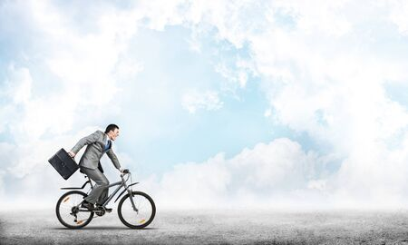 Man wearing business suit riding bicycle outdoor. Cyclist with suitcase on background of blue sky. Time management and business activity. Businessman hurrying to work. Business competition and career Archivio Fotografico