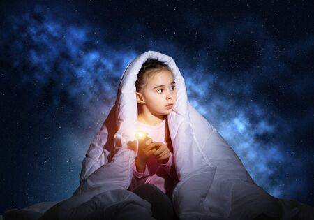 Frightened girl with flashlight hiding under blanket. Scared kid lying in his bed at home. Night terrors of child. Little girl can not sleep at night. Child in pajamas on background of deep blue sky