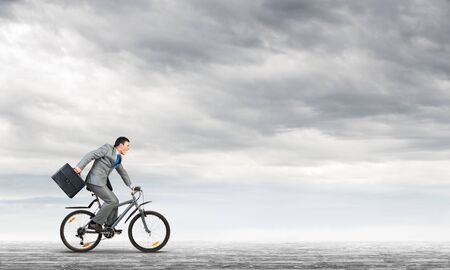 Man wearing business suit riding bicycle outdoor. Cyclist with suitcase on background of blue sky. Time management and business activity. Businessman hurrying to work. Business competition and career Stock Photo