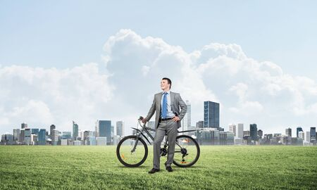 Pleasant man in business suit and tie standing on green grass with bike. Be active concept. Cheerful businessman with bicycle relax on green meadow at sunny day. Happy and successful business people Reklamní fotografie