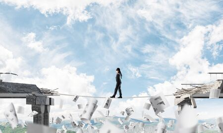 Businessman walking blindfolded on rope among flying papers and above huge gap in bridge as symbol of hidden threats and risks. Nature view on background. 3D rendering. Imagens