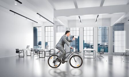 Manager in business suit riding bicycle at conference hall. Businessman with megaphone on bike at loft office interior. Business presentation and announcement. Handsome cyclist speaking in loudspeaker