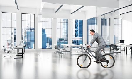 Businessman wearing business suit riding bicycle at modern business workspace. Business activity concept. Male cyclist at comfortable coworking space with big windows. New commercial real estate.