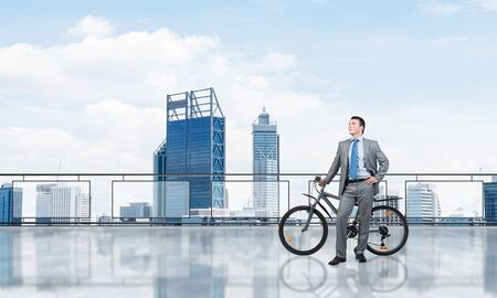 Young man wearing business suit standing on balcony with bike. Businessman with bicycle on background of blue sky above megalopolis. Male cyclist holding bicycle on terrace with modern downtown view.